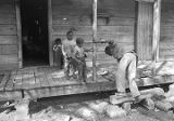 John Nixon trying to climb onto the porch of his house in Autaugaville, Alabama.