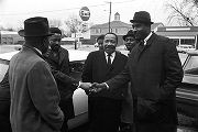 Hosea Williams, Martin Luther King, Jr., and other men, standing in the parking lot outside...