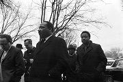 Martin Luther King, Jr., Hosea Williams, and other men, walking through a parking lot toward...