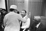 Martin Luther King, Jr., seated and shaking hands with a woman during a meeting at Maggie Street...