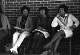 Three women sitting in front of a brick wall during a homecoming rally at Booker T. Washington...