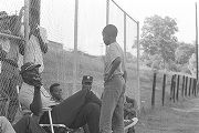 Man speaking to a young boy during a boys' baseball game, probably in Montgomery, Alabama.