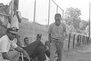 Men and children sitting in front of a fence on the edge of the field during a boys' baseball...
