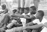 Young men sitting in front of a fence on the edge of the field during a boys' baseball game,...