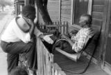 Johnny Burrell speaking to a man on the front porch of a small wooden house in Little Korea, a...