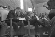 Andrew Young, Martin Luther King, Jr., and others sitting behind the podium during a meeting at...