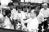 Man explaining scientific equipment to a group of students from Lee County, Alabama, during a...