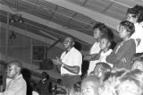 Audience standing in the bleachers during a gospel concert.