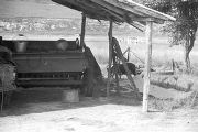 Trailer or agricultural equipment parked under a wooden garage in rural Lowndes County, Alabama.
