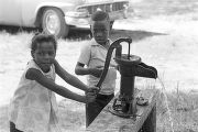 Children getting water from a hand pump outside, probably during a cookout.
