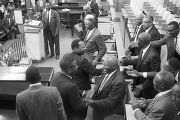 Martin Luther King, Jr., and Ralph Abernathy, shaking hands with men during a meeting at a large,...