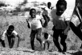 "Children running up the bank of ""The Big Ditch,"" a gravel quarry filled with water near..."