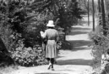 Woman walking down Clayton Alley, an unpaved road in Montgomery, Alabama.