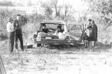 "People seated in and standing around a station wagon parked at a rest stop during the ""March..."
