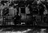 African American man and white woman seated in the yard in front of a cinder block house,...