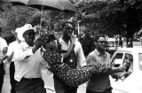 "Stokely Carmichael carrying a young woman down the road during the ""March Against Fear""..."