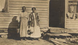Two African American women standing in front of a clapboard building.
