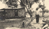 African American man standing beside a plow in the yard in front of a wooden shack, presumably in...