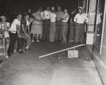 People gathered on a sidewalk in Phenix City, Alabama, the night Albert Patterson was assassinated.