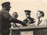 George Wallace shaking hands with an African American police officer.