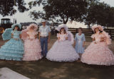 Governor Guy Hunt and his wife, Helen, standing with four young women in antebellum costumes at a...