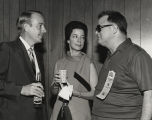 Albert and Martha Brewer speaking with another man indoors at the Alabama International Motor...