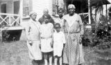 Adults and children standing in the yard of a house in Calhoun, Alabama.