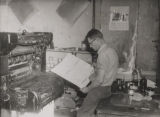 Man examining large sheet of paper in a print shop, probably in Dora, Alabama.