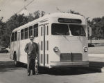 Man standing beside one of the first buses built by the Southern Coach Manufacturing Company in...