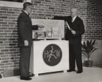 Two men placing products of the Scott Paper Company into a time capsule inside the foundation...