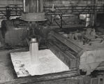"""Hot ingot being lofted by overhead crane from soaking pits at the Fairfield Steel Works of..."