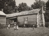 Women and children in front of a cabin in the former slaves' quarters of Joseph Wheeler's...