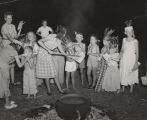 Children dressed as American Indians and eating corn on the cob, probably at a festival or party...