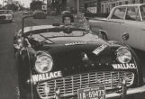 "Woman driving a Triumph convertible covered with ""Wallace"" stickers during the 1962..."