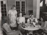"Students drinking sodas and reading letters on a ""loafing porch"" at Alabama College in..."