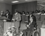 George Wallace seated in his wheelchair before an African American congregation.