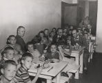 Several men eating lunch with young students at a school in Alabama.