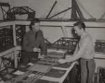 Two men studying the construction of floating bridges in an engineering class at Alabama...