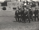 President John F. Kennedy, Governor George Wallace, and others, walking in front of a helicopter...