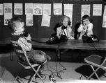 Three children talking on telephones while seated at a table in a classroom.