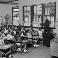 Priest calling on students with their hands raised in a classroom at Nazareth Catholic Mission in...
