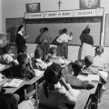 Children solving arithmetic problems on the blackboard in a classroom at Nazareth Catholic Mission...