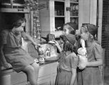 Four young Girl Scouts (Brownies) gathered around food items and cleaning products on a kitchen...