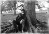 Probably Fred Pfaff, brother of Herman Pfaff, sitting at the base of a tree.