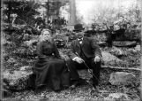 Margaret and Herman Pfaff seated on large rocks outdoors.