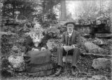 Louise and Charles Stetson seated on large rocks outdoors.