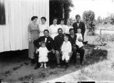 Members of the Davis family outside a wooden building.