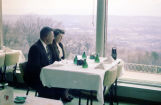 Mr. and Mrs. Roy Farnell observing the landscape from a large window inside a restaurant on...