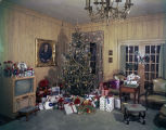 Living room decorated for Christmas, including a tree, presents, cards, and decorations.