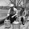 Man and little boy with oil cans in a truck bed, probably during the annual tour of the Autauga...